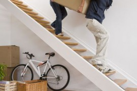 Couple carrying heavy moving box up stairs
