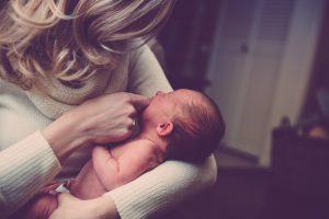 UN ammaman portant un bébé dans une maison