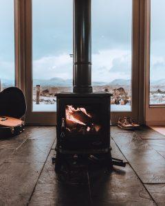un poêle à bois noir carré installé devant une grande baie vitrée