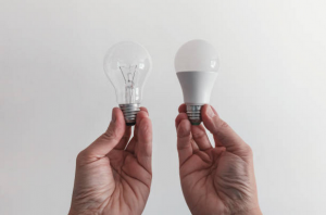 Deux mains qui tiennent chacune une ampoule électrique