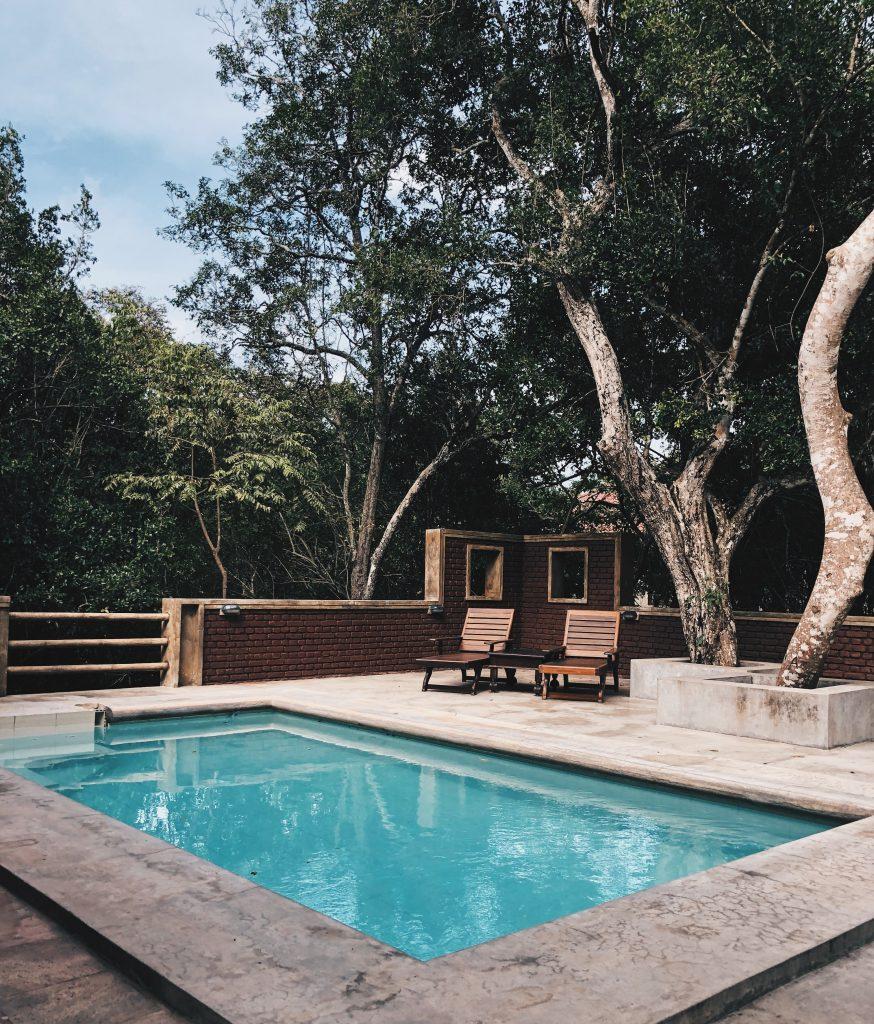 piscine en extérieur avec abord en béton et chaises longues en bois sous les arbres