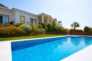 extérieur d'une maison avec une piscine et des arbustes