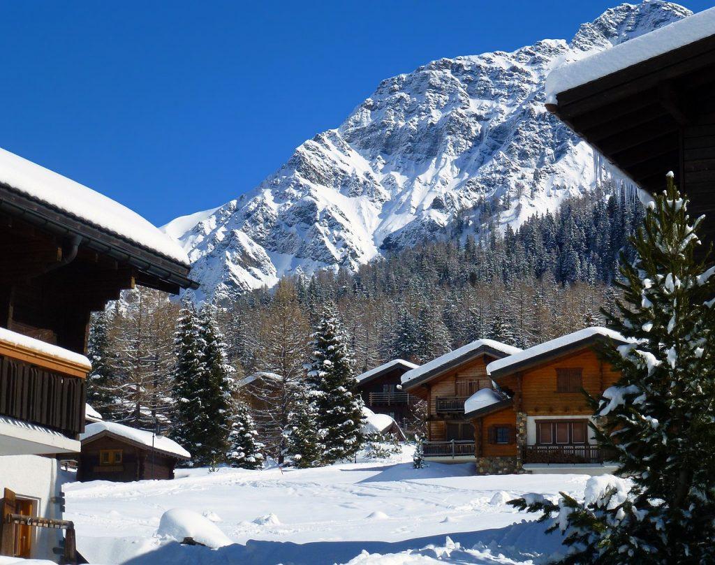 chalets enneigés face à la montagne sous un ciel bleu