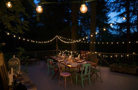 terrasse de nuit avec table à manger et guirlandes lumineuses