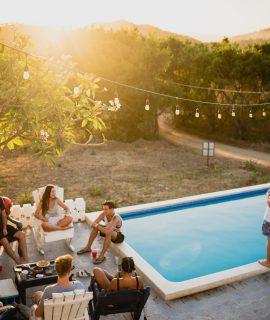 extérieur de maison avec piscine et guirlandes lumineuses avec personnes qui font la fête